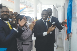 Mr Fiifi Kwetey (second -right) applauding after unveiling a plaque to open the Esich Life Assurance office.