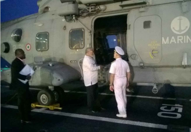 President Rawlings and Admiral Paul Treu view a huge helicopter on the deck of the Cavour.