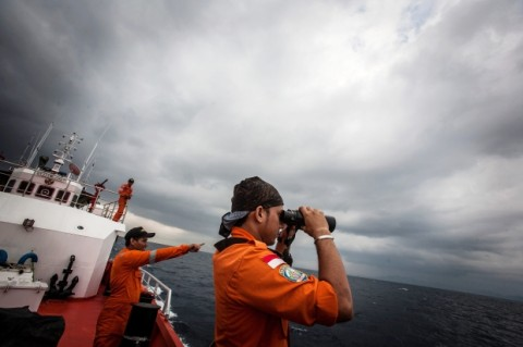 """Indonesian national search and rescue agency personel watch over high seas during a search operation for missing Malaysia Airlines flight MH370 in the Andaman Sea on March 15, 2014. Investigators now believe a Malaysian jet that vanished was commandeered by a """"skilled, competent"""" flyer who piloted the plane for hours, a senior Malaysian military official said on March 15 as Prime Minister Najib Razak prepared to address the nation. Photograph by: CHAIDEER MAHYUDDIN , AFP/Getty Images"""