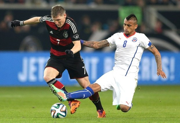Germany midfielder Bastian Schweinsteiger rides a challenge from Chile's Arturo Vidal