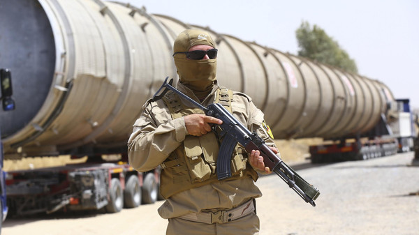 A member of the Kurdish security forces takes up position with his weapon as he guards a section of an oil refinery, which is being brought on a truck to Kalak refinery in the outskirts of Arbil