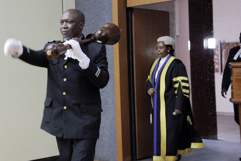 The sergeant at arms ushers in the former Eala speaker Margaret Zziwa during a session in Kigali last October. (John Mbanda)