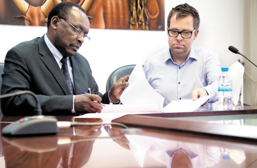 Kanimba (L) and Banks sign paperwork yesterday. (T. Kisambira)