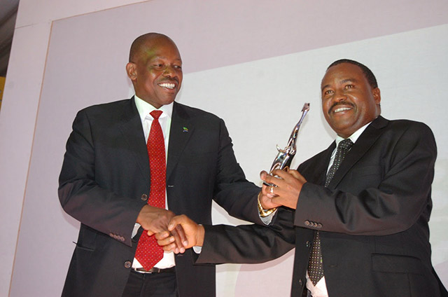 Deputy Minister for Energy and Minerals, Mr Charles Kitwanga (left) presents a trophy to the winner of the inaugural Best Board Leadership Awards (BBLA) 2014 in the Banking Sector, the CRDB Bank Acting Chairman of the Board, Mr Martin Mmari. CRDB Bank emerged the winner in the banking sector, while Heritage Insurance became victor in the insurance sector at a colourful ceremony at Serena Hotel in Dar es Salaam over the weekend.