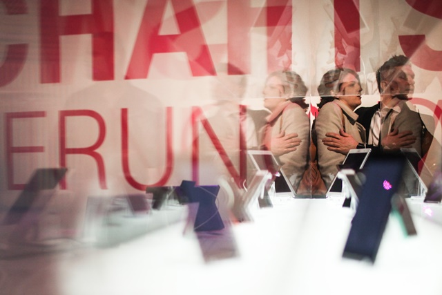 """Staff members look on in front of a cell phone dispaly booth at Deutsche Telekom's stand at 2015 CeBIT Technology Trade fair in Hanover, Germany, on March 16, 2015. Top IT business fair CeBIT 2015, which features a strong Chinese presence, opened on Sunday in Germany (The banner reads """"Economical Wonder 4.0""""). (Xinhua/Zhang Fan)"""
