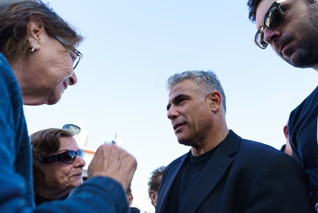 """Yair Lapid (2nd R), Israel's """"Yesh Atid"""" Party leader and former Finance Minister, talks to local residents during an elections campaign tour in Haifa, northern Israel, on March 16, 2015, one day before parliamentary elections. (Xinhua/JINI)"""