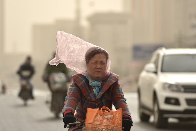 A woman rides in dusty wind with veil on face on a road in Tianjin, north China, March 28, 2015. Part of Tianjin received dusty weather on Saturday. (Xinhua/Yue Yuewei) (zwx)