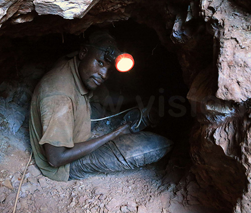 A gold miner in Lukingi breaks rocks in search of the precious metal