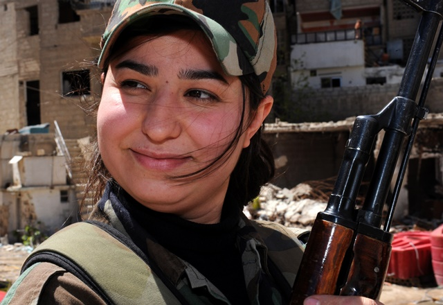 A female sniper reacts in Daraya suburb of the capital Damascus, Syria, on April 5, 2015. The snipers are members of the female force in Syrian Republican Guards. Their unit consists of around 800 volunteer, unmarried, female fighters- aged between 20 and 24 years old. Their task is to work alongside the Syrian army in its battle against the rebels.  (Xinhua/Zhang Naijie) (jl)