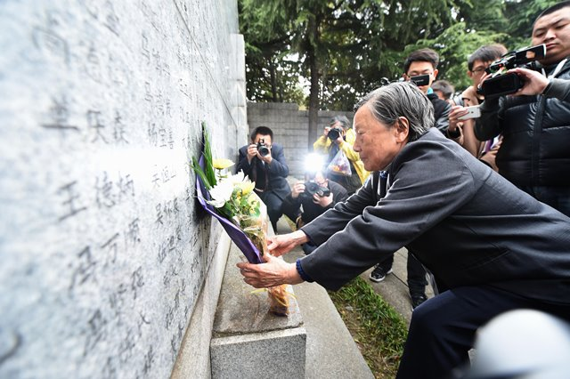 Survivor of Nanjing Massacre Xia Shuqin lays flowers in front of a wall inscribed the name list of victims at the Memorial Hall of the Victims in Nanjing Massacre by Japanese Invaders on the Qingming Festival in Nanjing, capital of east China's Jiangsu Province, April 5, 2015. Japanese troops captured Nanjing, then China's capital, on Dec. 13 of 1937 and started a 40-odd-day slaughter. More than 300,000 Chinese soldiers who had laid down their arms and civilians were murdered, and over 20,000 women were raped. (Xinhua/Sun Can) (lfj)