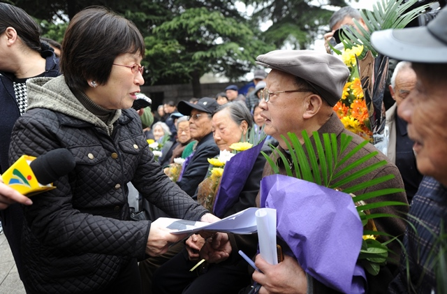 Tamaki Matsuoka (L), head of the Japan-China Peace Research Organization, talks with survivors of Nanjing Massacre in a ceremony to mourn the Nanjing Massacre victims at the Memorial Hall of the Victims in Nanjing Massacre by Japanese Invaders on the Qingming Festival in Nanjing, capital of east China's Jiangsu Province, April 5, 2015. Japanese troops captured Nanjing, then China's capital, on Dec. 13 of 1937 and started a 40-odd-day slaughter. More than 300,000 Chinese soldiers who had laid down their arms and civilians were murdered, and over 20,000 women were raped. (Xinhua/Han Yuqing) (lfj)
