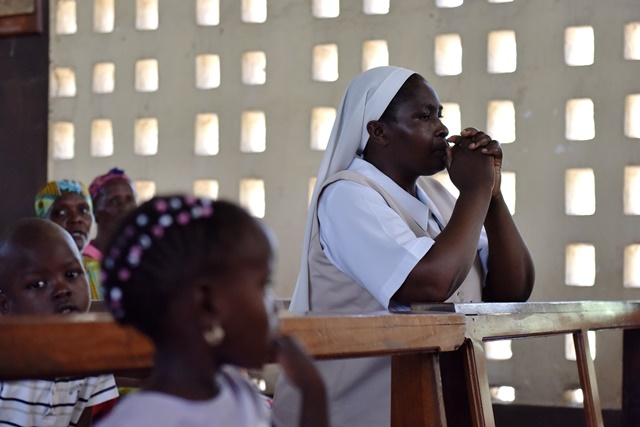 A nun prays during a commemorating service to mourn the victims during the campus attack in Garissa, Kenya, April 5, 2015.