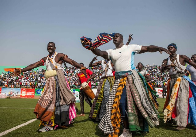 """Supporters of Balla Gaye 2 dance for good luck before the Senegalese traditional wrestling match """"Le Choc"""" at Demba Diop Stadium, Dakar, capital of Senegal, April 5, 2015. Thousands of audience have watched the biggest match here on Sunday at the beginning of the wrestling season with the most famous wrestlers Balla Gaye 2 and Eumeu Sene competing. Eumeu Sene won the match at last. (Xinhua/Li Jing)"""