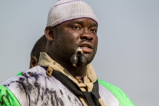 """Eumeu Sene performs mysterious ritual before the Senegalese traditional wrestling match """"Le Choc"""" at Demba Diop Stadium, Dakar, capital of Senegal, April 5, 2015. Thousands of audience have watched the biggest match here on Sunday at the beginning of the wrestling season with the most famous wrestlers Balla Gaye 2 and Eumeu Sene competing. Eumeu Sene won the match at last. (Xinhua/Li Jing)"""