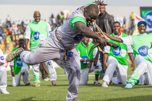 """Eumeu Sene dances for his supporters before the Senegalese traditional wrestling match """"Le Choc"""" at Demba Diop Stadium, Dakar, capital of Senegal, April 5, 2015. Thousands of audience have watched the biggest match here on Sunday at the beginning of the wrestling season with the most famous wrestlers Balla Gaye 2 and Eumeu Sene competing. Eumeu Sene won the match at last. (Xinhua/Li Jing)"""