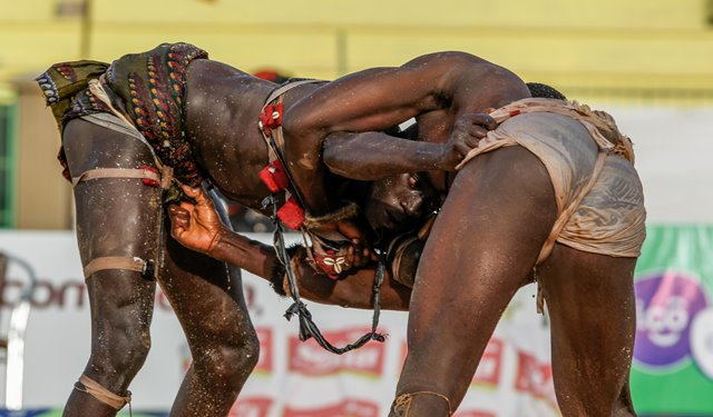 """Wrestlers compete in the Senegalese traditional wrestling match """"Le Choc"""" at Demba Diop Stadium, Dakar, capital of Senegal, April 5, 2015. Thousands of audience have watched the biggest match here on Sunday at the beginning of the wrestling season with the most famous wrestlers Balla Gaye 2 and Eumeu Sene competing. Eumeu Sene won the match at last. (Xinhua/Li Jing)"""