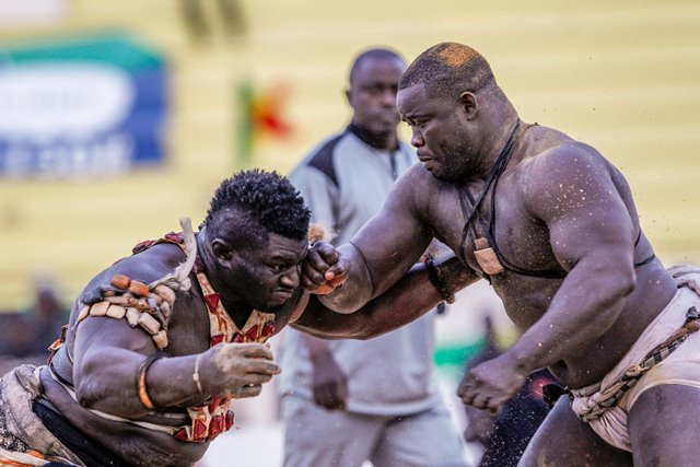 """Balla Gaye 2 (L) competes with Eumeu Sene during the Senegalese traditional wrestling match """"Le Choc"""" at Demba Diop Stadium, Dakar, capital of Senegal, April 5, 2015. Thousands of audience have watched the biggest match here on Sunday at the beginning of the wrestling season with the most famous wrestlers Balla Gaye 2 and Eumeu Sene competing. Eumeu Sene won the match at last. (Xinhua/Li Jing)"""