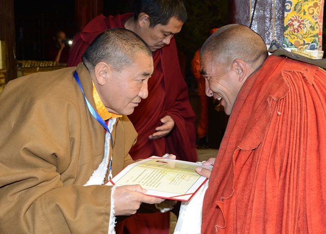 A monk (R) receives his certificate at the awarding ceremony for Gexe Lharampa, the highest academic degree in Tibetan Buddhism studies, at the Jokhang Monastery in Lhasa, capital of southwest China's Tibet Autonomous Region, April 5, 2015. After rounds of tests and debating sessions, ten monks received the Gexe Lharampa degree this year, a title similar to a doctorate in the Gelugba faction of Tibetan Buddhism. Gexe means knowledgeable and Lharampa represents the highest degree among the four ranks in the Gexe system. (Xinhua/Chogo) (yxb)