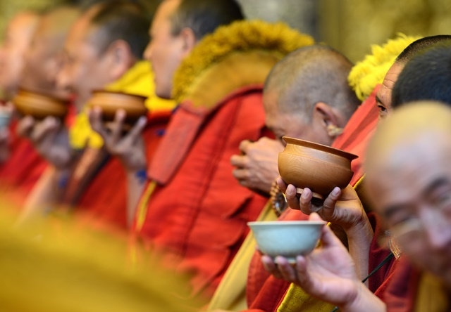 Monks drink tea at the awarding ceremony for Gexe Lharampa, the highest academic degree in Tibetan Buddhism studies, at the Jokhang Monastery in Lhasa, capital of southwest China's Tibet Autonomous Region, April 5, 2015. After rounds of tests and debating sessions, ten monks received the Gexe Lharampa degree this year, a title similar to a doctorate in the Gelugba faction of Tibetan Buddhism. Gexe means knowledgeable and Lharampa represents the highest degree among the four ranks in the Gexe system. (Xinhua/Chogo) (yxb)