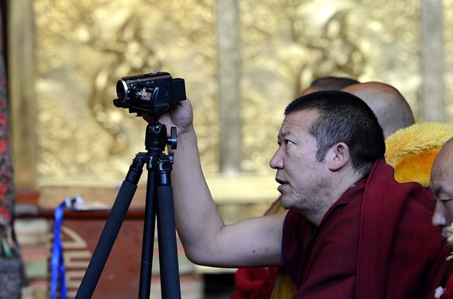 A monk takes photos during the awarding ceremony for Gexe Lharampa, the highest academic degree in Tibetan Buddhism studies, at the Jokhang Monastery in Lhasa, capital of southwest China's Tibet Autonomous Region, April 5, 2015. After rounds of tests and debating sessions, ten monks received the Gexe Lharampa degree this year, a title similar to a doctorate in the Gelugba faction of Tibetan Buddhism. Gexe means knowledgeable and Lharampa represents the highest degree among the four ranks in the Gexe system. (Xinhua/Chogo) (yxb)