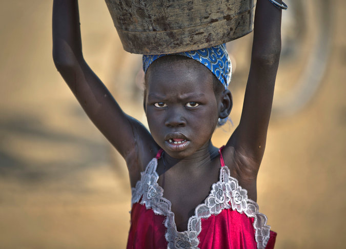 A displaced girl carrying water to a United Nations compound in South Sudan. Violence there has uprooted 180,000 people. Credit Ben Curtis/Associated Press