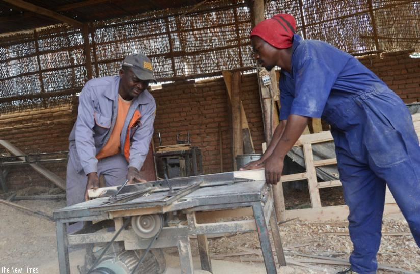 Byiringiro (L) with one of his employees at his workshop in Musanze District. (Jean d'Amour Mbonyinshuti)