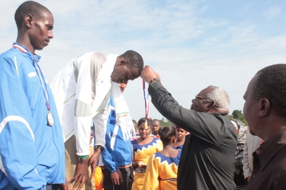 Zanzibar Second Vice-President, Ambassador Seif Ali Idd, decorates the 1,500 metres winner Gabriel Gerald of Arusha with a gold medal at the 54th National Athletics Championship at the Filbert Bayi Secondary School at Mkuza, Kibaha in Coast Region yesterday. (Photo by Cosmas Mlekani)