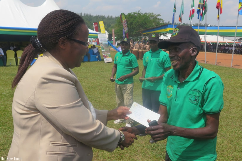 A farmer receives a cheque of Rwf100,000 from minister Mukeshimana. (Moses Opobo)